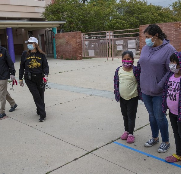Families wearing masks gather outside San Fernando Senior High School in April 2020. (Mel Melcon / Los Angeles Times)