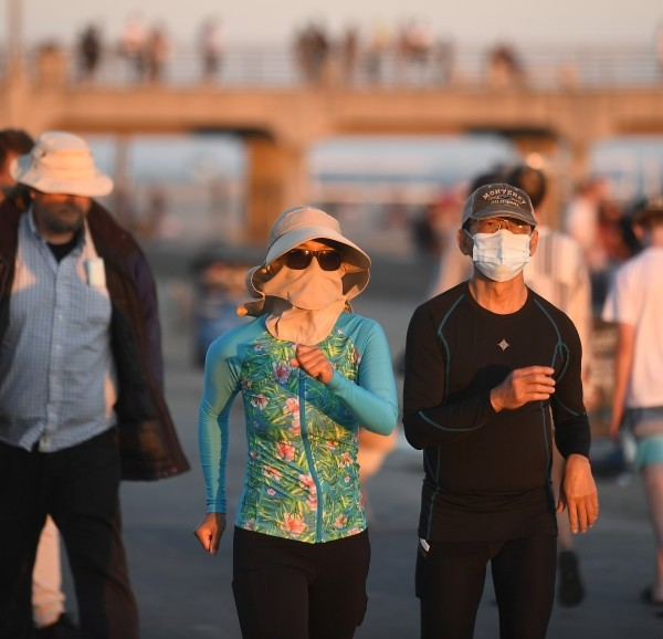 People walk along the strand in Huntington Beach in this undated photo. (Wally Skalij / Los Angeles Times)