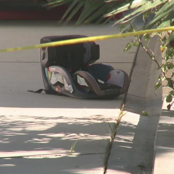 A child's car seat remains at the scene where a toddler was left in a hot car in Fullerton on July 8, 2020. (KTLA)