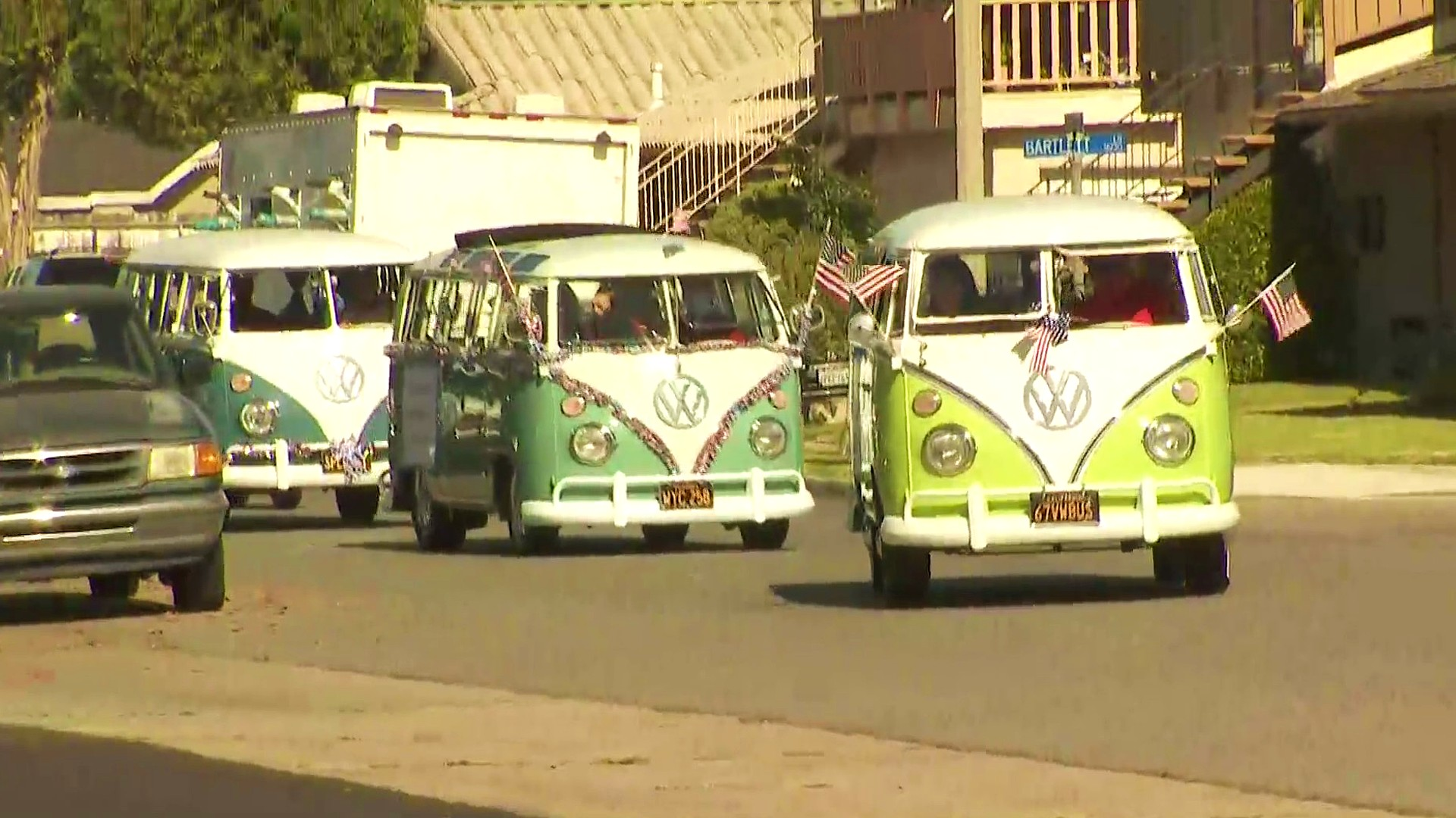 Volkswagen busses are seen amid the Huntington Beach parade on July 4, 2020. (KTLA)
