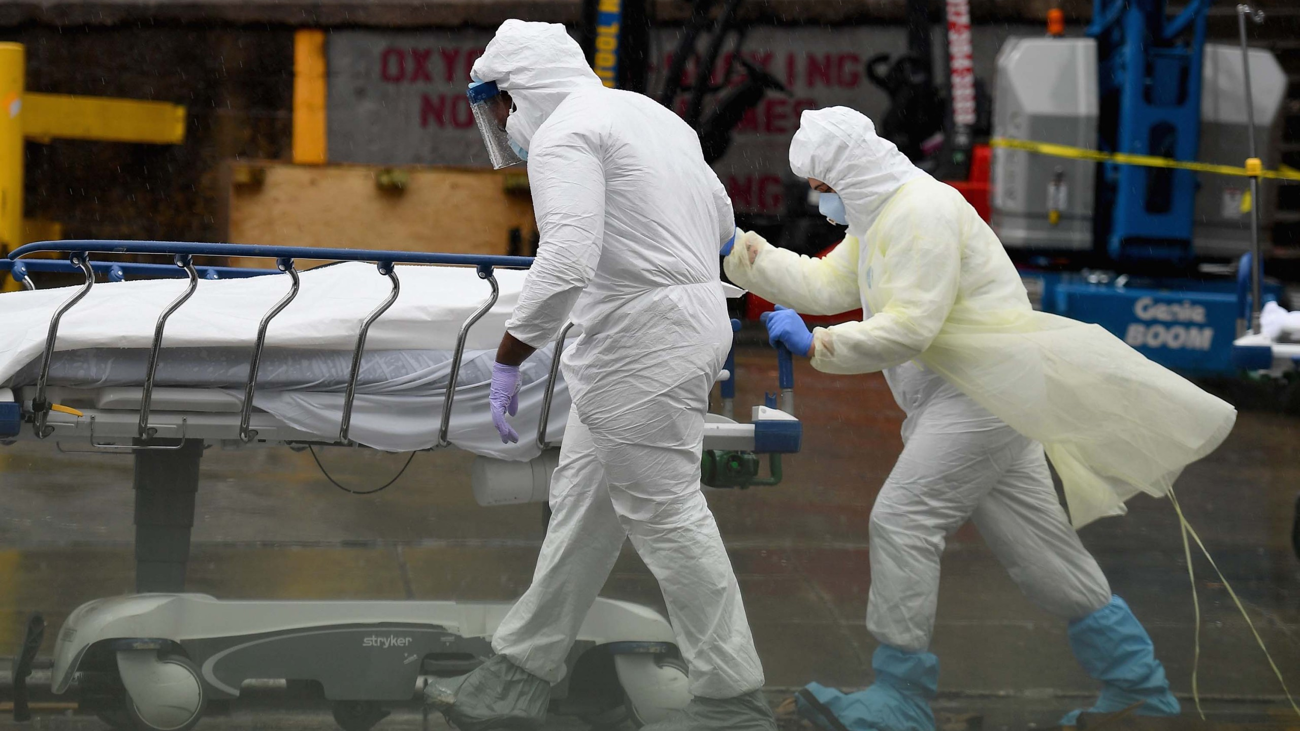 Medical personnel move a deceased patient to a refrigerated truck serving as make shift morgues at Brooklyn Hospital Center on April 09, 2020 in New York City. (ANGELA WEISS/AFP via Getty Images)