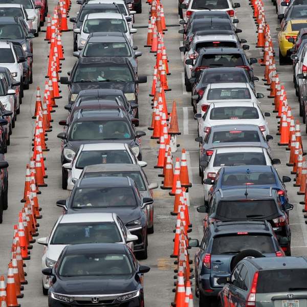 Lines of cars wait at a drive-through coronavirus testing site outside Hard Rock Stadium in Miami Gardens, Fla. Florida health officials say the state has reached a grim milestone: more than 200,000 people have tested positive for the novel coronavirus since the start of the outbreak. (AP Photo/Wilfredo Lee)