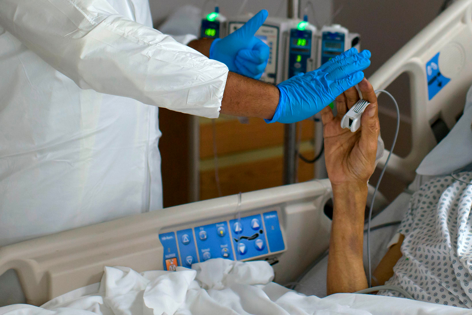 A healthcare worker high-fives a patient in the COVID-19 Unit at United Memorial Medical Center in Houston, Texas, July 2, 2020. (MARK FELIX/AFP via Getty Images)