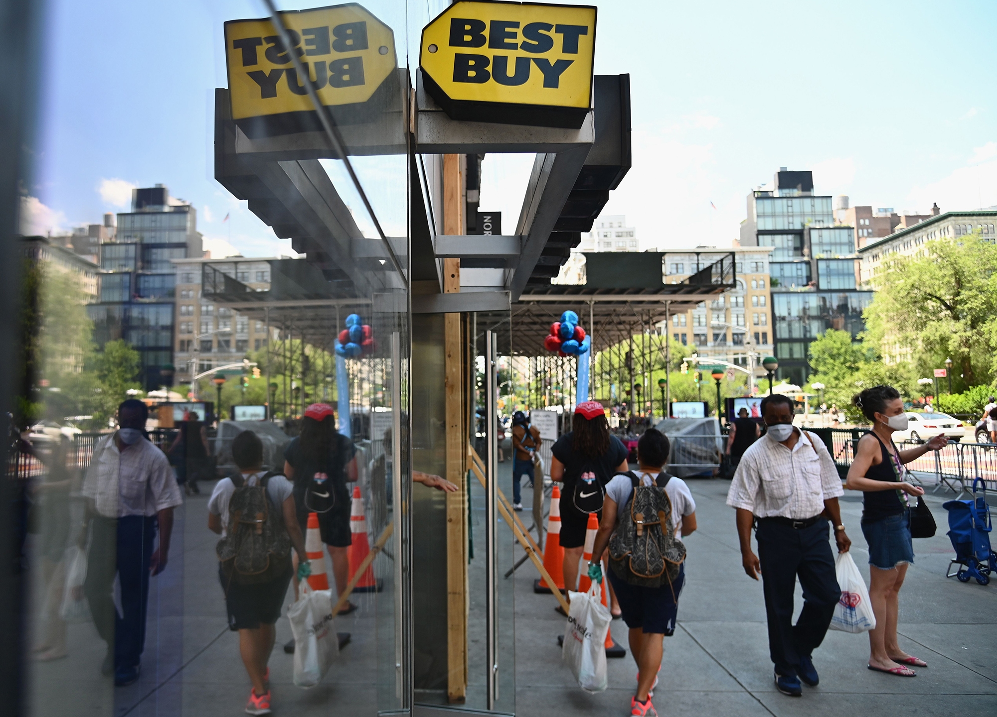 People wearing facemasks walk past a Best Buy store near Union Square on June 25, 2020 in New York City. (ANGELA WEISS/AFP via Getty Images)