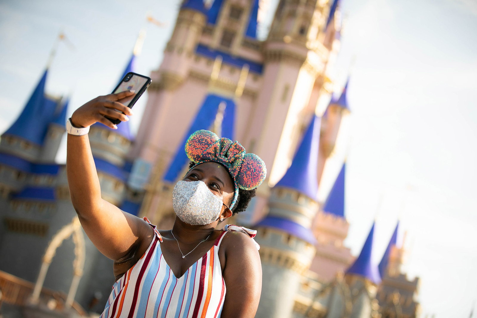 In this handout photo provided by Walt Disney World Resort, a guest stops to take a selfie at Magic Kingdom Park at Walt Disney World Resort on July 11, 2020 in Lake Buena Vista, Florida. July 11, 2020 is the first day of the phased reopening. (Olga Thompson/Walt Disney World Resort via Getty Images)