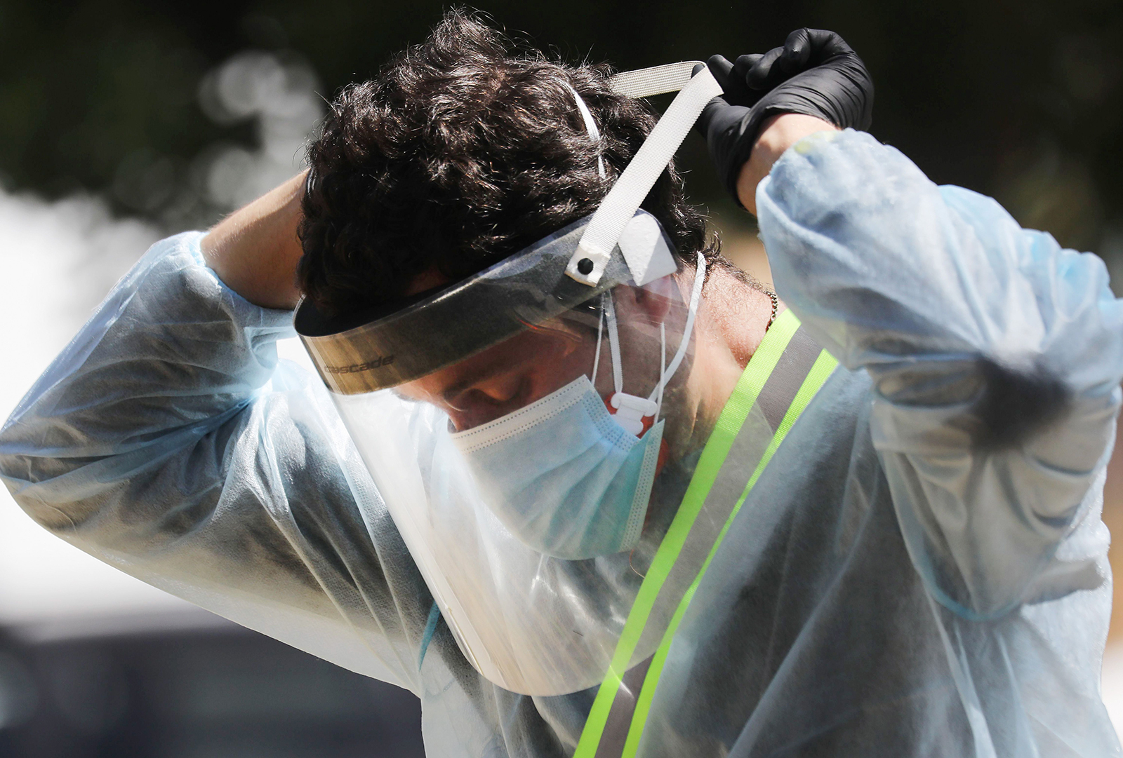 A COVID-19 testing associate adjusts his personal protective equipment (PPE) at a testing center at Lincoln Park amid the coronavirus pandemic on July 07, 2020 in Los Angeles, California. There has been a spike in new coronavirus cases in California along with an increase in the overall positivity rate and number of hospitalizations. (Mario Tama/Getty Images)