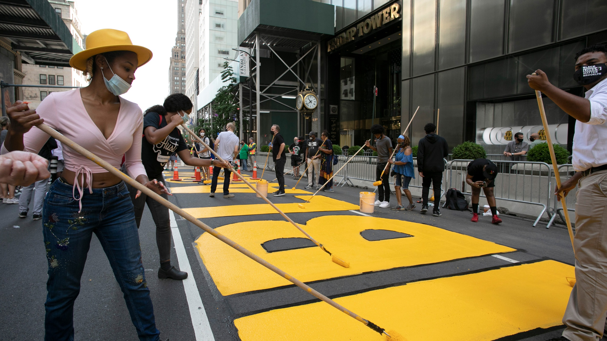 Azia Toussaint, left, participates in the painting of Black Lives Matter on Fifth Avenue in front of Trump Tower, Thursday, July 9, 2020, in New York. (AP Photo/Mark Lennihan)