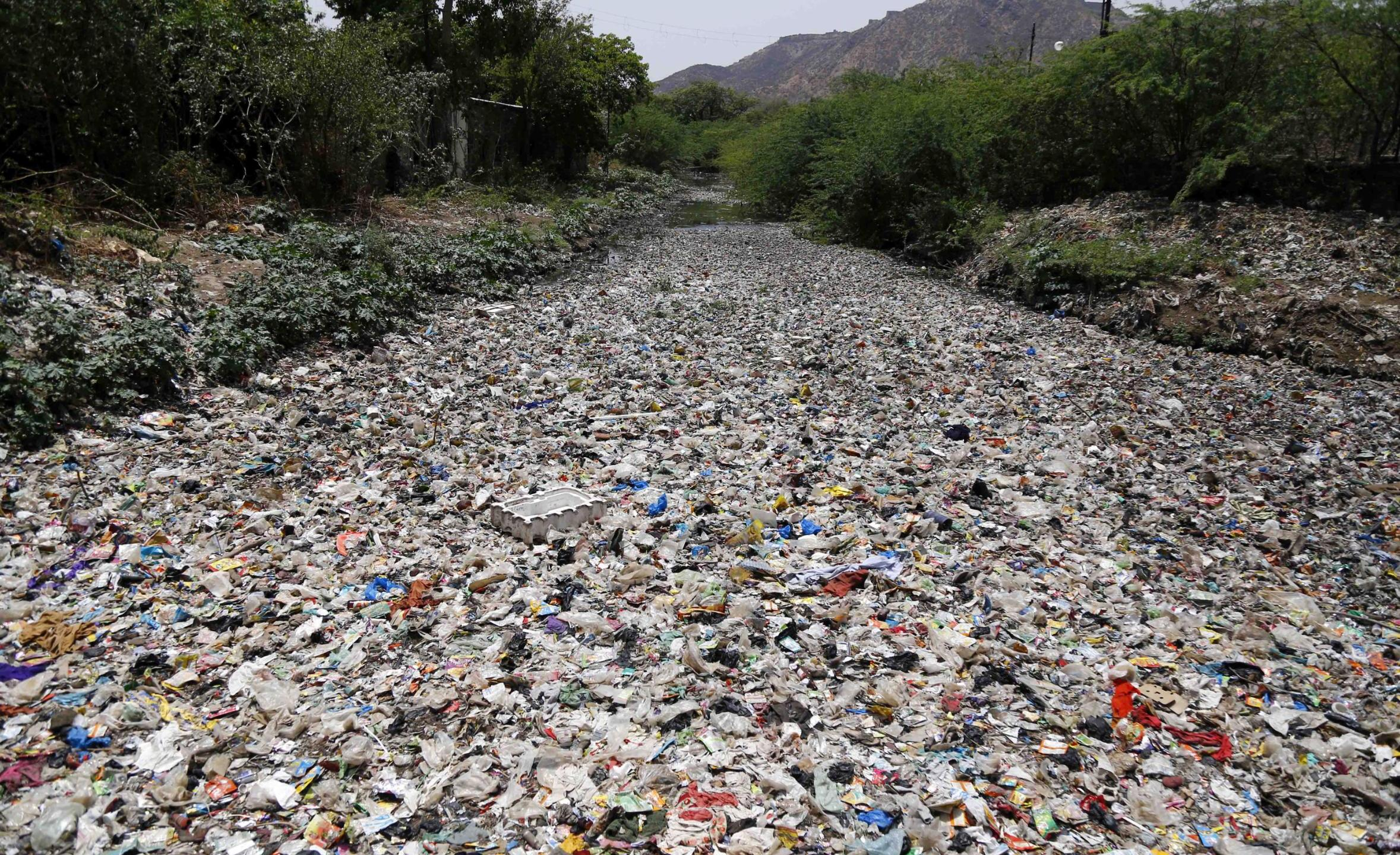 The world will have 710 million tons of plastic pollution by 2040 despite efforts to cut waste, study says. The image shows garbage floating along a river in Ajmer in the Indian state of Rajasthan on May 8, 2018. (HIMANSHU SHARMA/AFP/AFP/Getty Images)