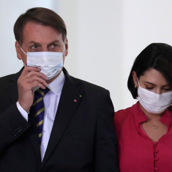 Wearing masks to curb the spread of the new coronavirus, Brazil's President Jair Bolsonaro and his wife Michelle Bolsonaro, arrive to attend the launching of a rights guarantee program for rural women, at the Planalto Presidential Palace in Brasilia, Brazil, Wednesday, July 29, 2020. (AP Photo/Eraldo Peres)