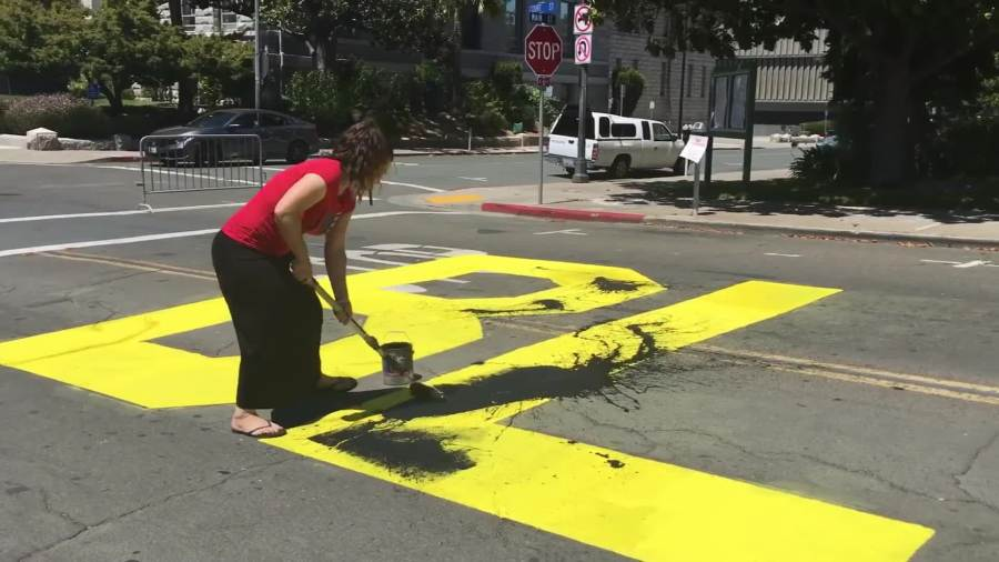 A woman paints over a Black Lives Matter mural in Martinez. (Youtube/Kerry Leidich via CNN)