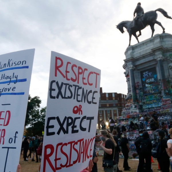 In this Tuesday June 23, 2020, file photo protesters gather near the statue of Confederate General Robert E. Lee on Monument Avenue in Richmond, Va. (AP Photo/Steve Helber, FILE)