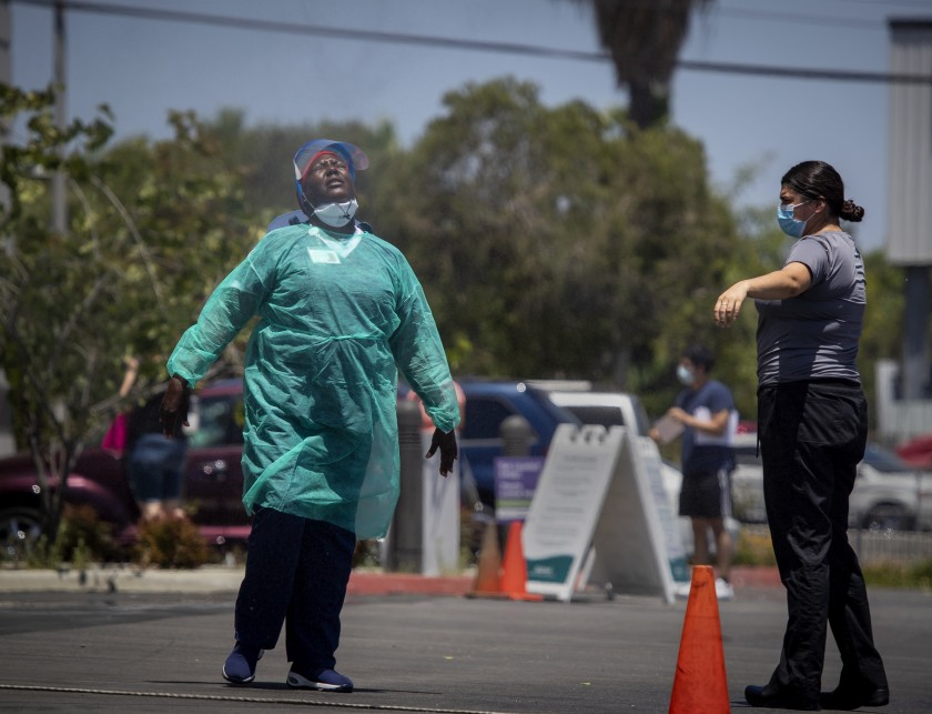 Wilma Thomas, a registered nurse, left, and Viviana Robles, a licensed practical nurse, cool off amid a heatwave while taking a break from administering coronavirus tests at AltaMed Health Services in Anaheim on July 9, 2020. (Allen J. Schaben/ Los Angeles Times)