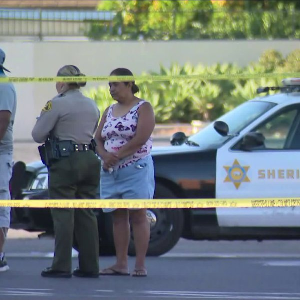 People stand near the scene of a reported carjacking that left a 13-year-old girl dead. The crime started in Pico Rivera and ended in El Monte, where the suspect was taken into custody. (KTLA)