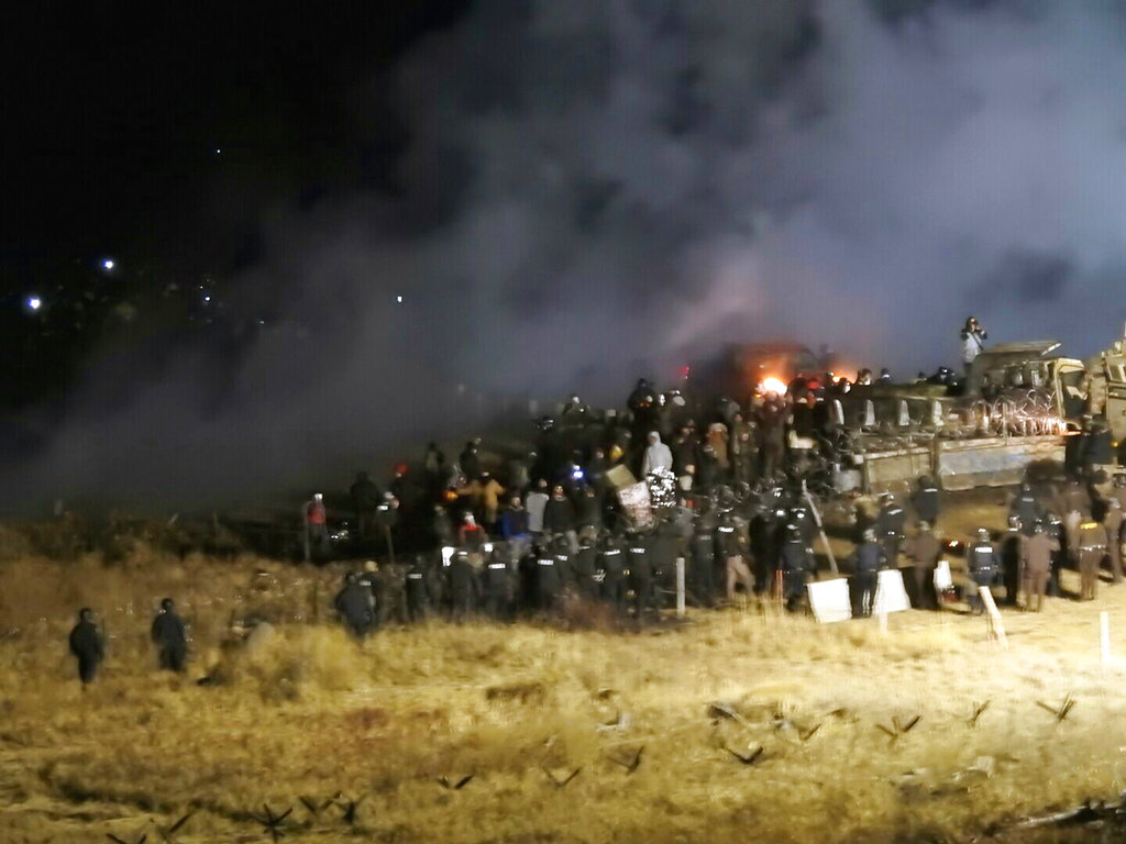In this file photo, provided by Morton County Sheriff's Department, law enforcement and protesters clash near the site of the Dakota Access pipeline on Sunday, Nov. 20, 2016, in Cannon Ball, N.D. A federal judge on Monday, July 6, 2020 sided with the Standing Rock Sioux Tribe and ordered the Dakota Access pipeline to shut down until more environmental review is done. (Morton County Sheriff's Department via AP, File)