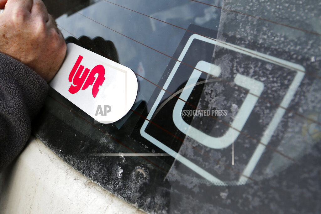 A Lyft logo is installed on a driver's car next to an Uber sticker in Pittsburgh on Jan. 31, 2018. (AP Photo/Gene J. Puskar, File)