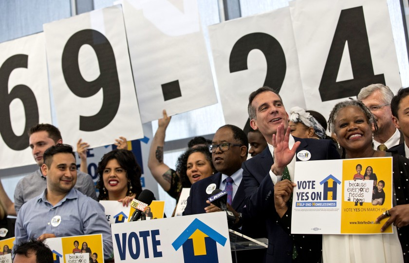 L.A. County Supervisor Mark Ridley-Thomas, center, and Los Angeles Mayor Eric Garcetti, are seen celebrating the passage of Measure H in 2017. (Brian van der Brug / Los Angeles Times)