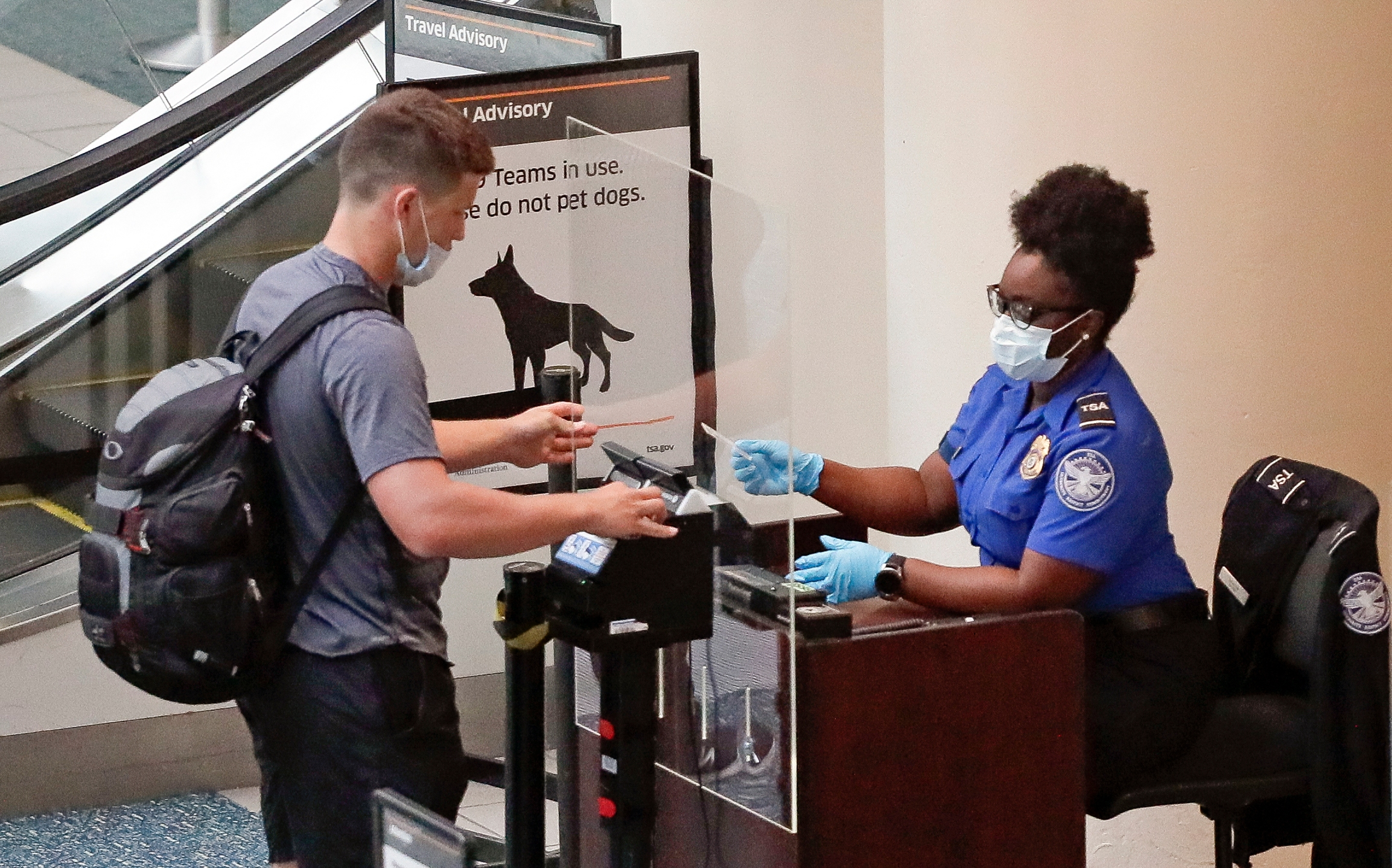 In this June 17, 2020 file photo, a TSA worker, right, checks a passenger before entering a security screening at Orlando International Airport in Orlando, Fla. (AP Photo/John Raoux, File)