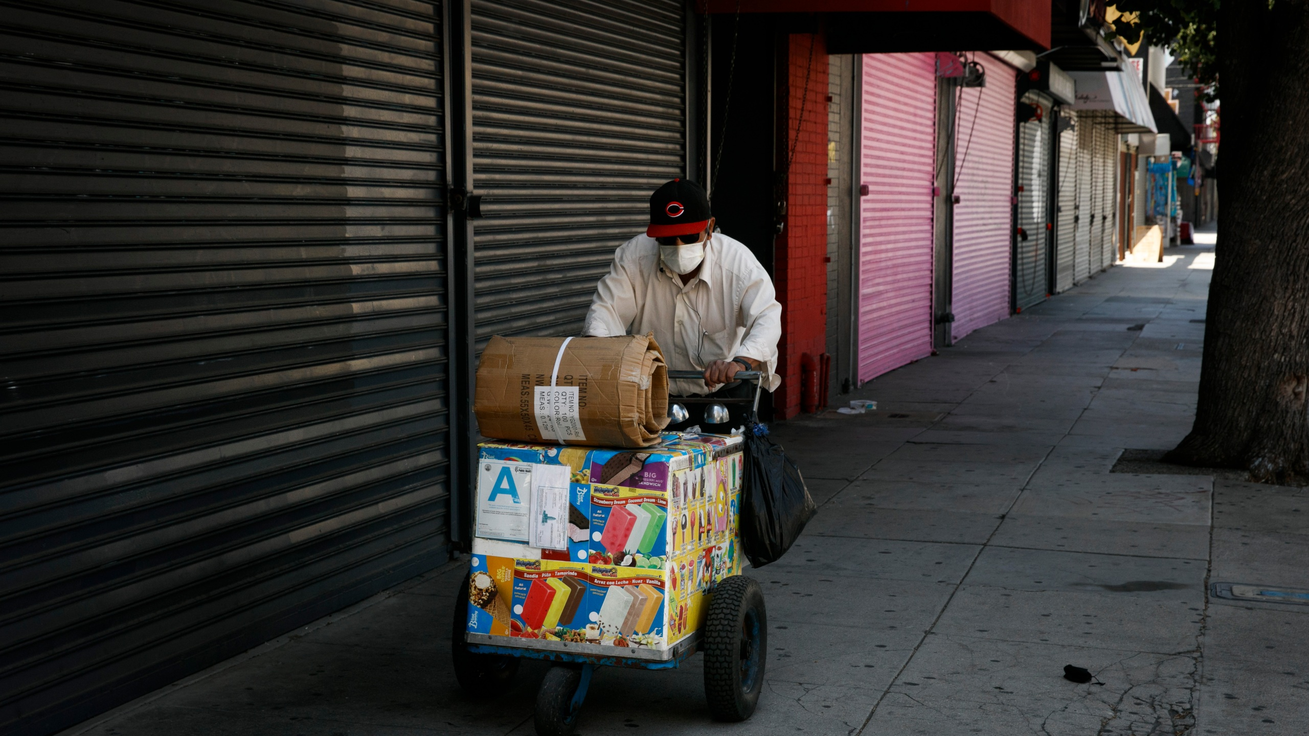 An ice cream vendor pushes his cart past shuttered stores during the coronavirus pandemic in Los Angeles on July 17, 2020. (AP Photo/Jae C. Hong)