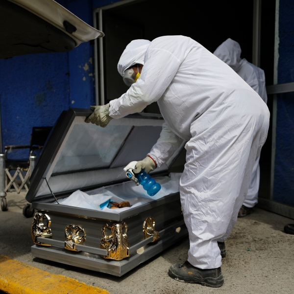 A worker wearing protective gear sprays disinfectant solution inside the coffin of a person who died from suspected COVID-19, as the body arrives at the crematorium at Xilotepec Cemetery in Xochimilco, Mexico City, Monday, July 27, 2020. (AP Photo/Rebecca Blackwell)