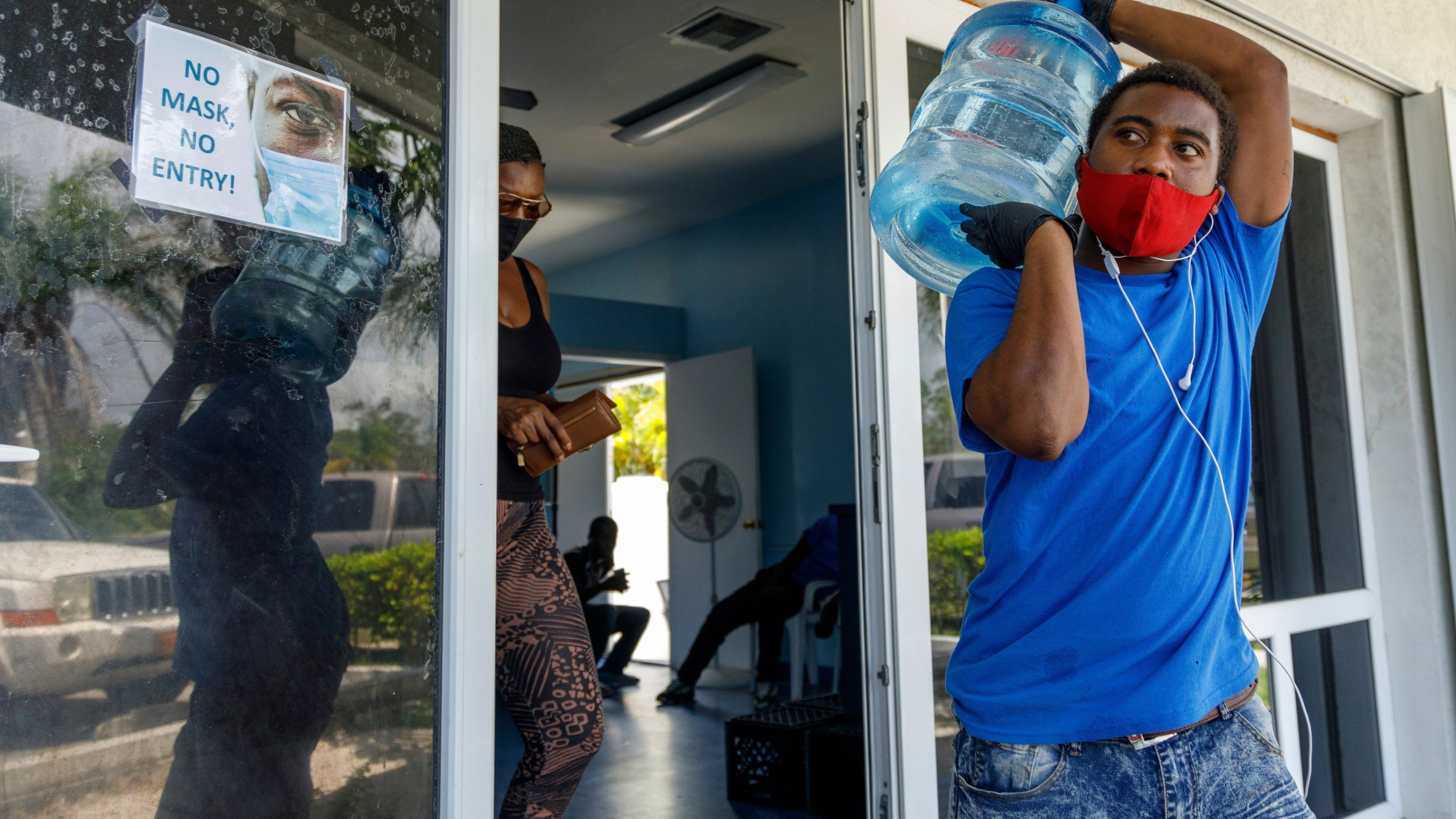 A man carries drinking water for a customer at a water depot store before the arrival of Hurricane Isaias in Freeport, Grand Bahama, Bahamas, on July 31, 2020. (AP Photo/Tim Aylen)