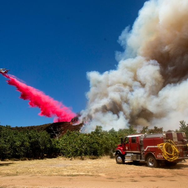 An air tanker drops fire retardant to a brush fire at the Apple Fire in Cherry Valley, Calif., Saturday, Aug. 1, 2020. (AP Photo/Ringo H.W. Chiu)