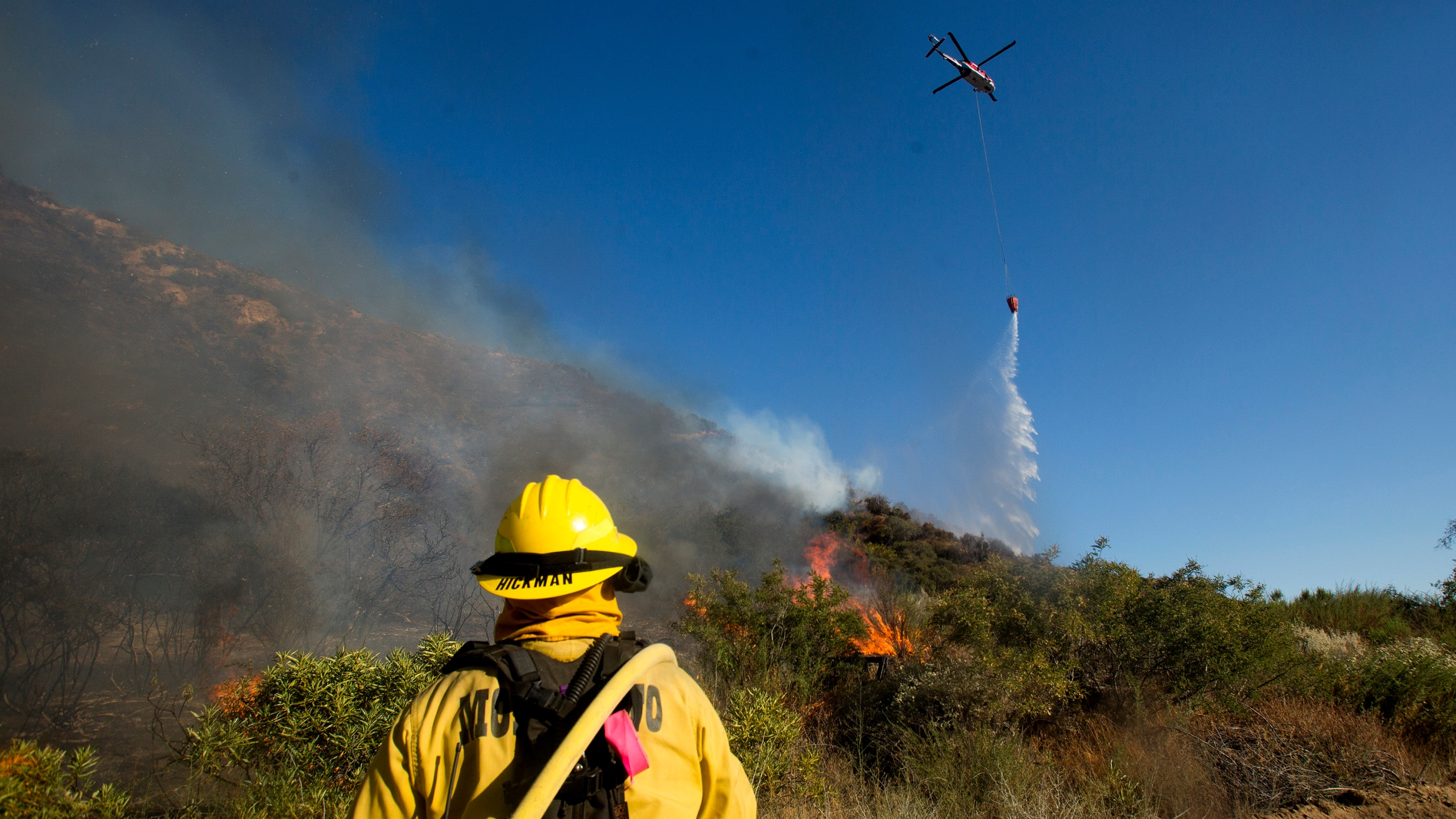 A firefighter watches as a helicopter drops water onto the Apple Fire near Banning, Calif., Sunday, Aug. 2, 2020. (AP Photo/Ringo H.W. Chiu)