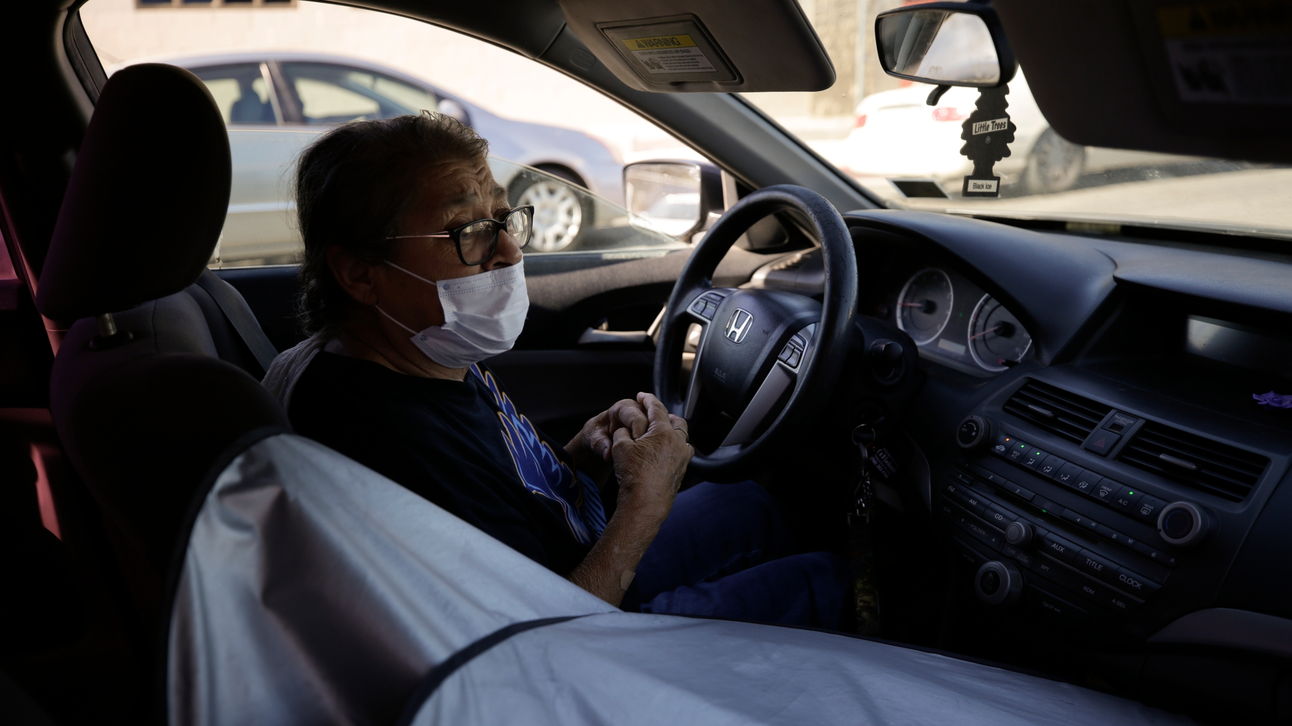 Marta Rosales waits in line for food at a distribution center Thursday, July 23, 2020, in Brawley, Calif. Rosales, who suffers from various health issues, rarely leaves her home during the coronavirus outbreak. She says the food she receives at the distribution center has been a savior. (AP Photo/Gregory Bull)