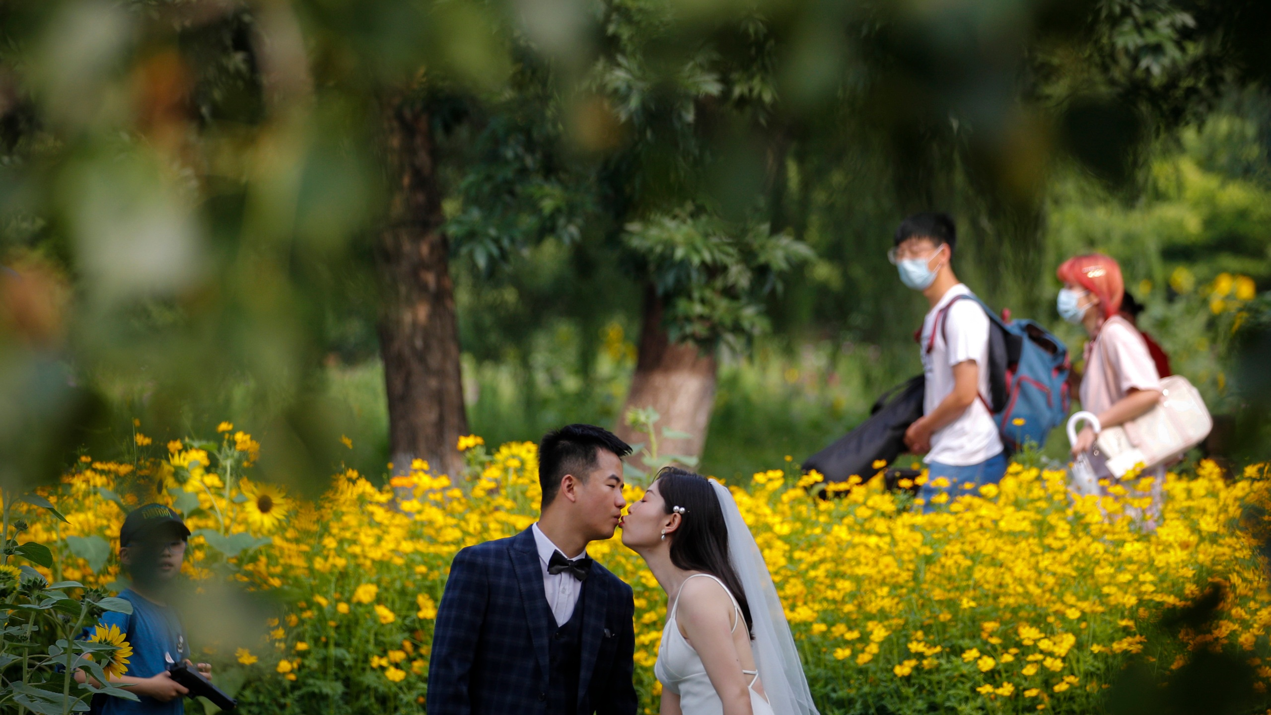 People wearing face masks pass by newlyweds kissing as they posing for wedding photos at the Olympic Forest Park in Beijing on July 2, 2020. (AP Photo/Andy Wong)