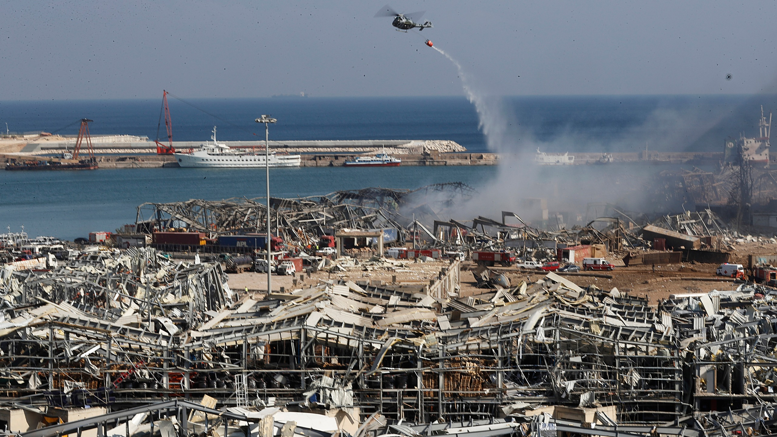 A Lebanese army helicopter throw water at the scene where an explosion hit the seaport of Beirut, Lebanon, Wednesday, Aug. 5, 2020. (AP Photo/Hussein Malla)