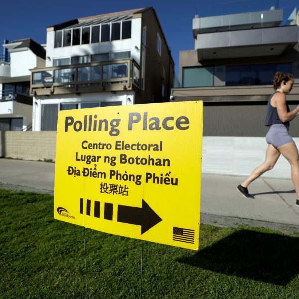 A woman runs on a path by a polling place during primary elections in San Diego on March 3, 2020. (Gregory Bull / Associated Press)