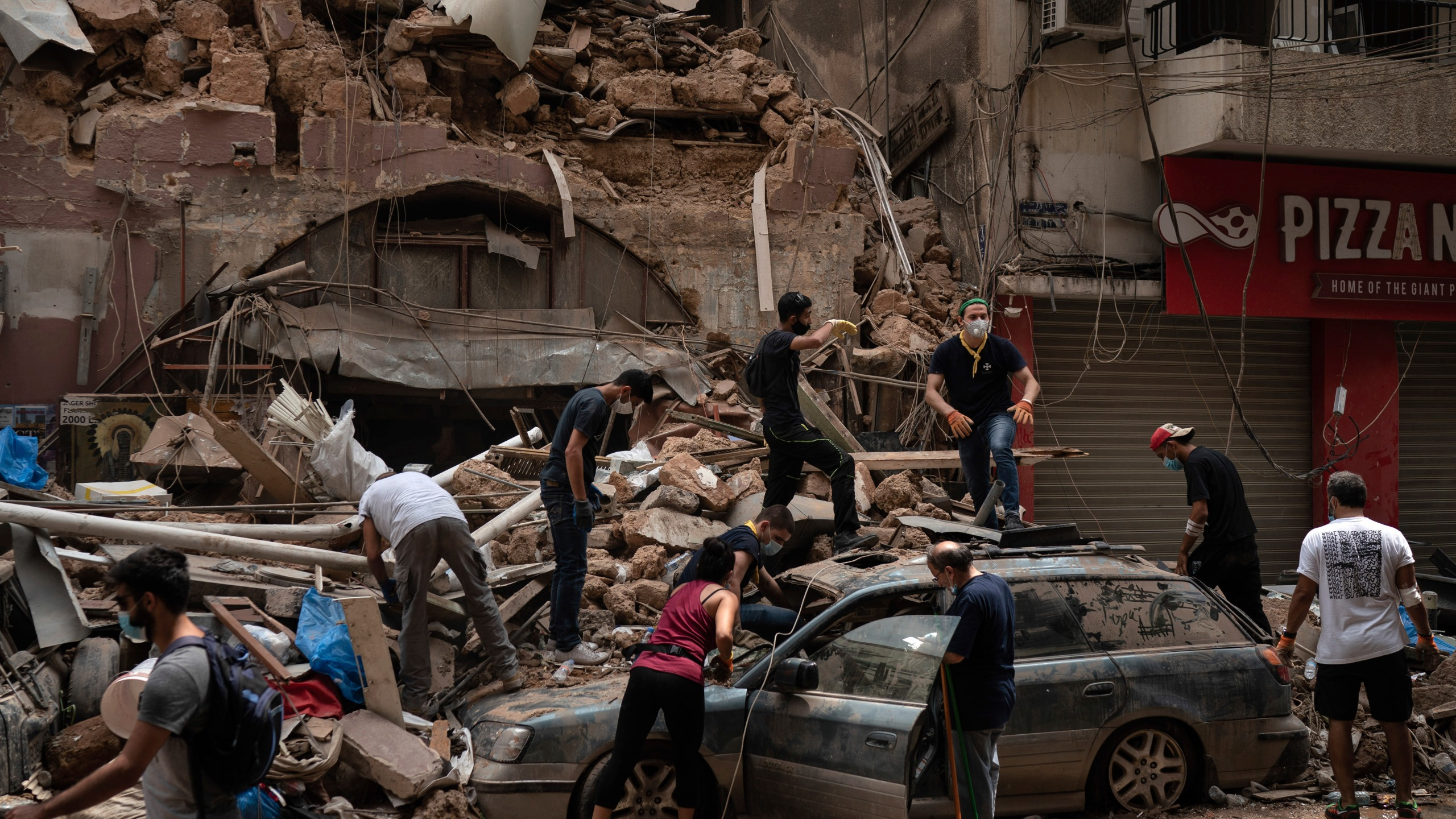People remove debris from a house damaged by Tuesday's explosion in the seaport of Beirut, Lebanon, Friday, Aug. 7, 2020. (AP Photo/Felipe Dana)