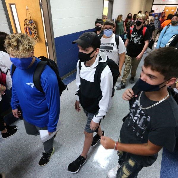 Guntown Middle School eighth graders walk the halls to their next class as others wait in their assigned spots against the wall before moving into their next class during the first day back to school for the Lee County District in Guntown, Miss. on Aug. 6, 2020. (Adam Robison/The Northeast Mississippi Daily Journal via AP, File)