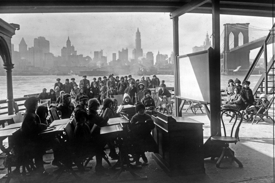This 1911 photo from the Library of Congress shows schoolchildren on the ferry boat Rutherford, across the river from Manhattan, and near the Brooklyn Bridge, at right, in New York. (Library of Congress via AP)