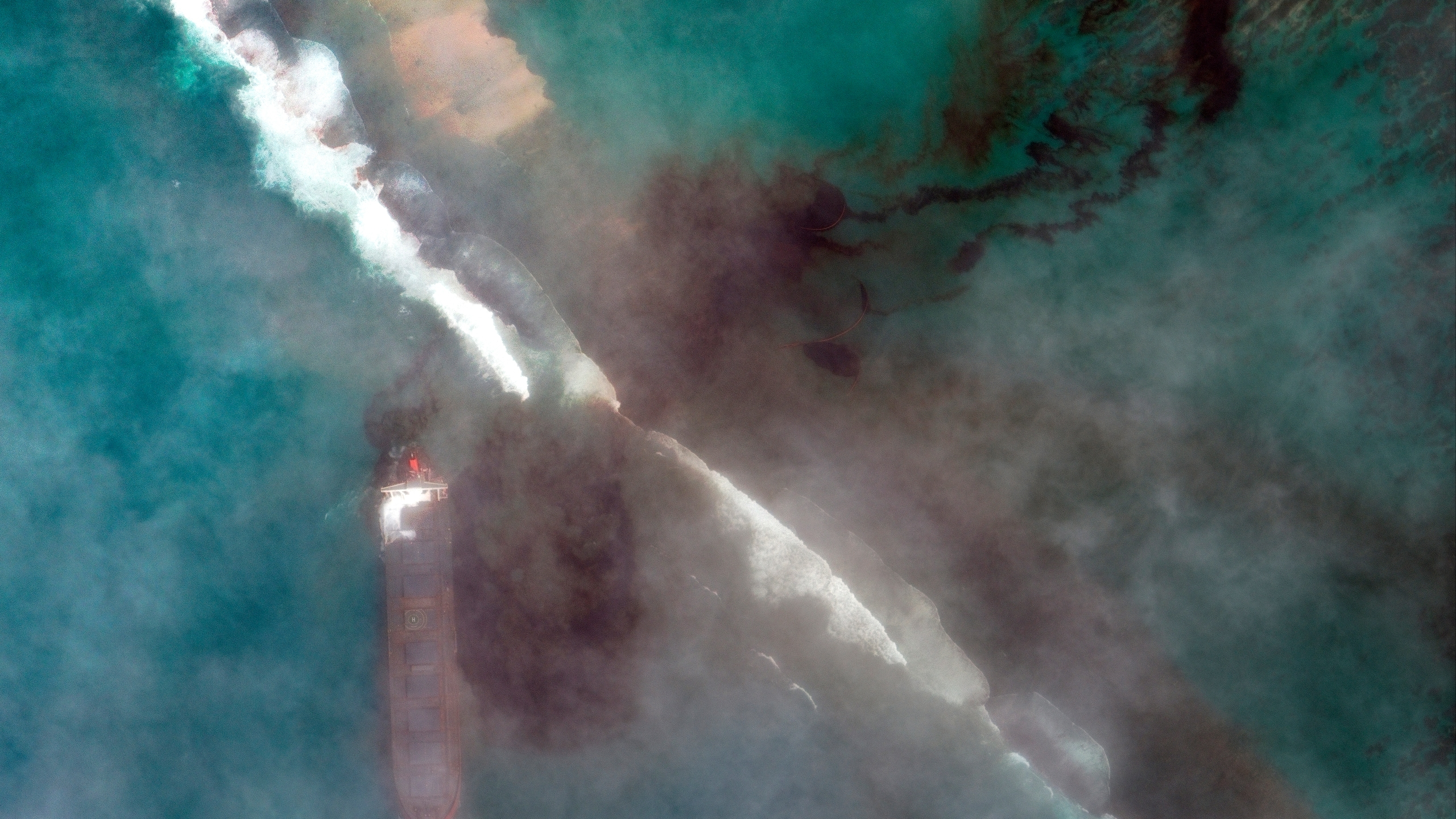 In this satellite image provided by 2020 Maxar Technologies on Aug. 7, 2020, an aerial view of oil leaking from the MV Wakashio, a bulk carrier ship that recently ran aground off the southeast coast of Mauritius. The prime minister of Mauritius says the government is appealing to France for help with a brewing environmental disaster after a ship that ran aground almost two weeks ago off the Indian Ocean island nation began leaking oil. ( 2020 Maxar Technologies via AP)