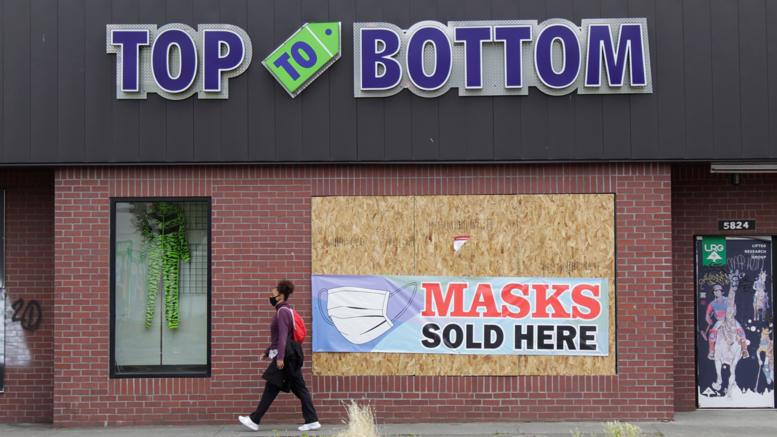 In this July 1, 2020, file photo, a woman walks past a business damaged during recent protests in North Portland, a historically Black neighborhood in Oregon. (AP Photo/Gillian Flaccus, File)