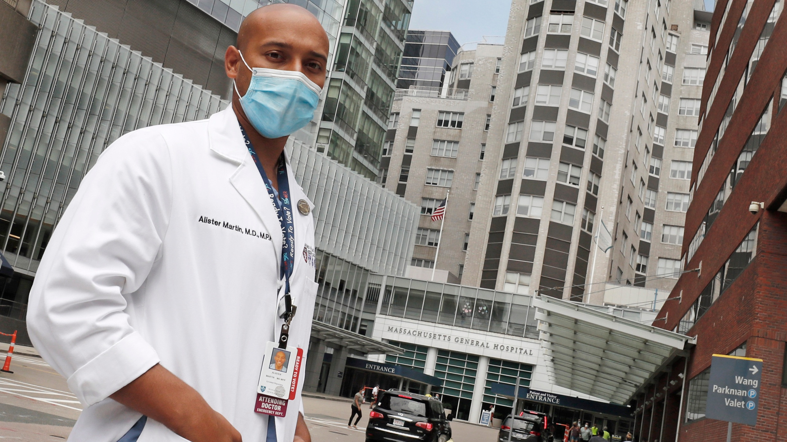 "Alister Martin, an emergency room doctor at Massachusetts General Hospital, poses outside the hospital, Friday, Aug. 7, 2020, in Boston. Martin founded the organization ""VotER"" to provide medical professionals voter registration resources for patients who are unregistered voters. (AP Photo/Charles Krupa)"