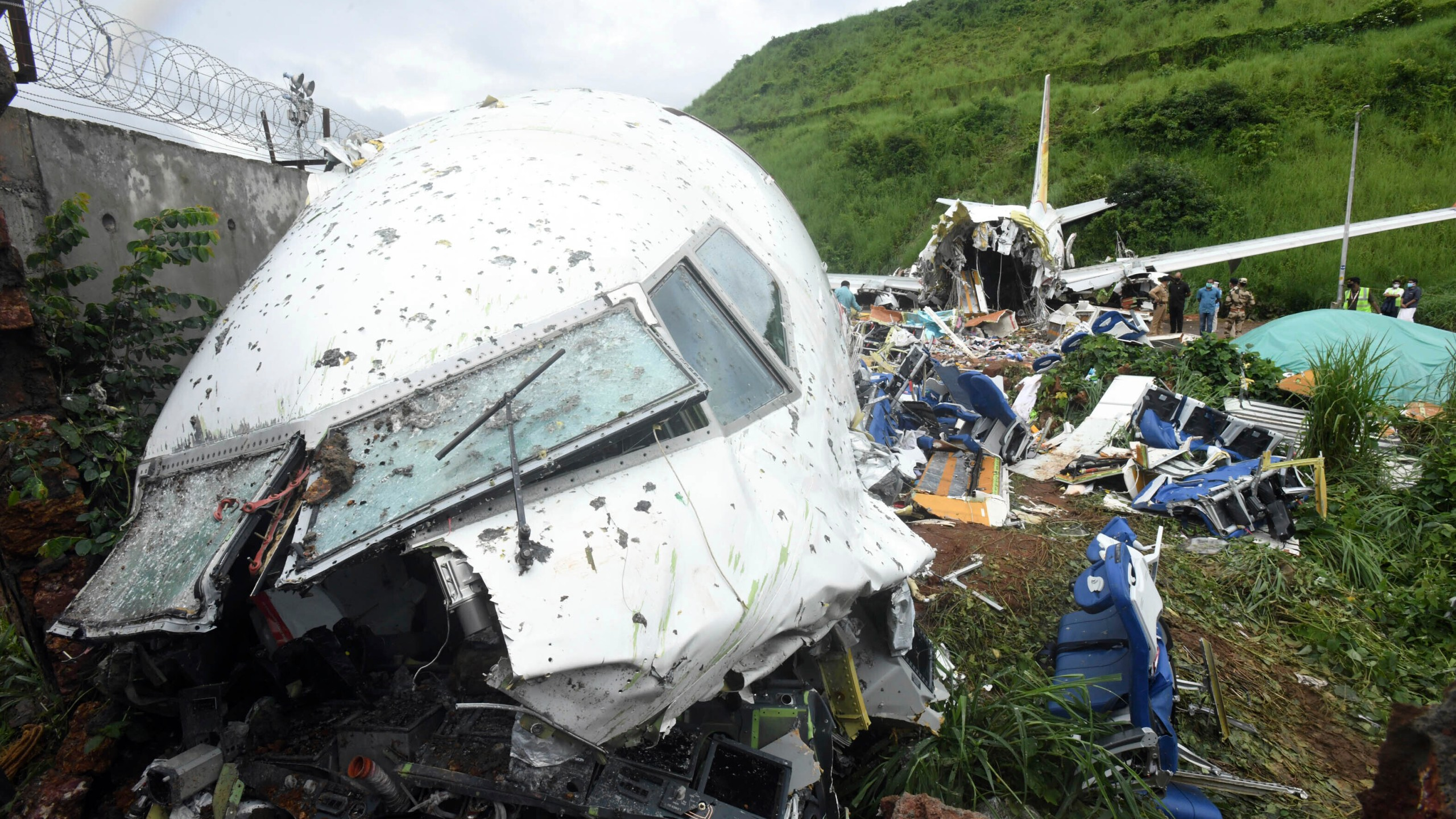 People stand by the debris of the Air India Express flight that skidded off a runway while landing in Kozhikode, Kerala state, India on Aug. 8, 2020. (AP Photo/Shijith Sreedhar)