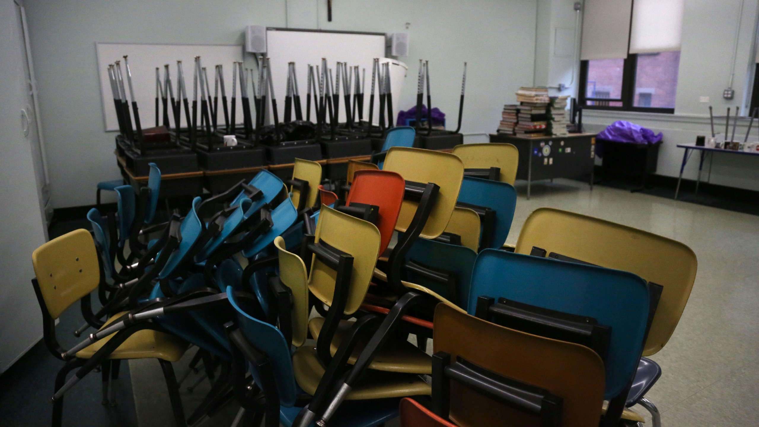 Desks are stacked in an empty classroom after the permanent closure of Queen of the Rosary Catholic Academy in Brooklyn borough of New York, Thursday, Aug. 6, 2020. (AP Photo/Jessie Wardarski)