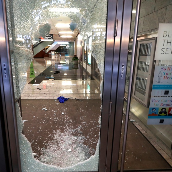 A door to the Block 37 retail building is shattered Monday, Aug. 10, 2020, after vandals struck overnight in Chicago's famed Loop. Chicago's police commissioner says more than 100 people were arrested following a night of looting and unrest that left several officers injured and caused damage in the city's upscale Magnificent Mile shopping district and other parts of the city. (AP Photo/Charles Rex Arbogast)