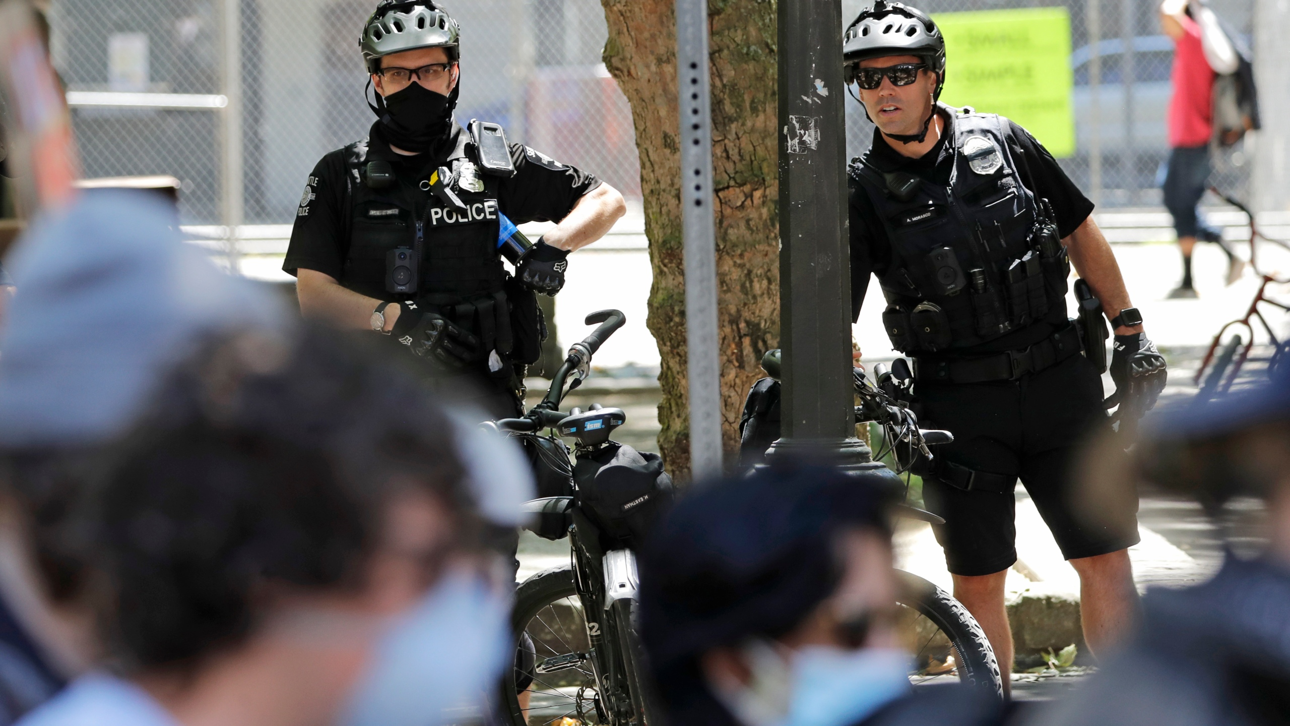 In this July 20, 2020, file photo, police officers look on at protesters in Seattle. (AP Photo/Elaine Thompson, File)