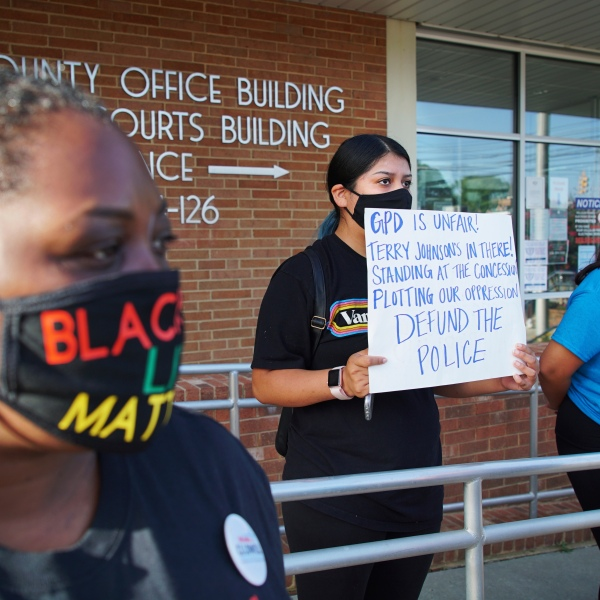Aranza Sosa, center, holds a sign at a protest in front of the Alamance County government building in Graham, N.C., on Monday, Aug. 3, 2020. Sosa, who was born in Mexico and is now a U.S. citizen, says the county is a hostile place for people of color. (AP Photo/Allen G. Breed)