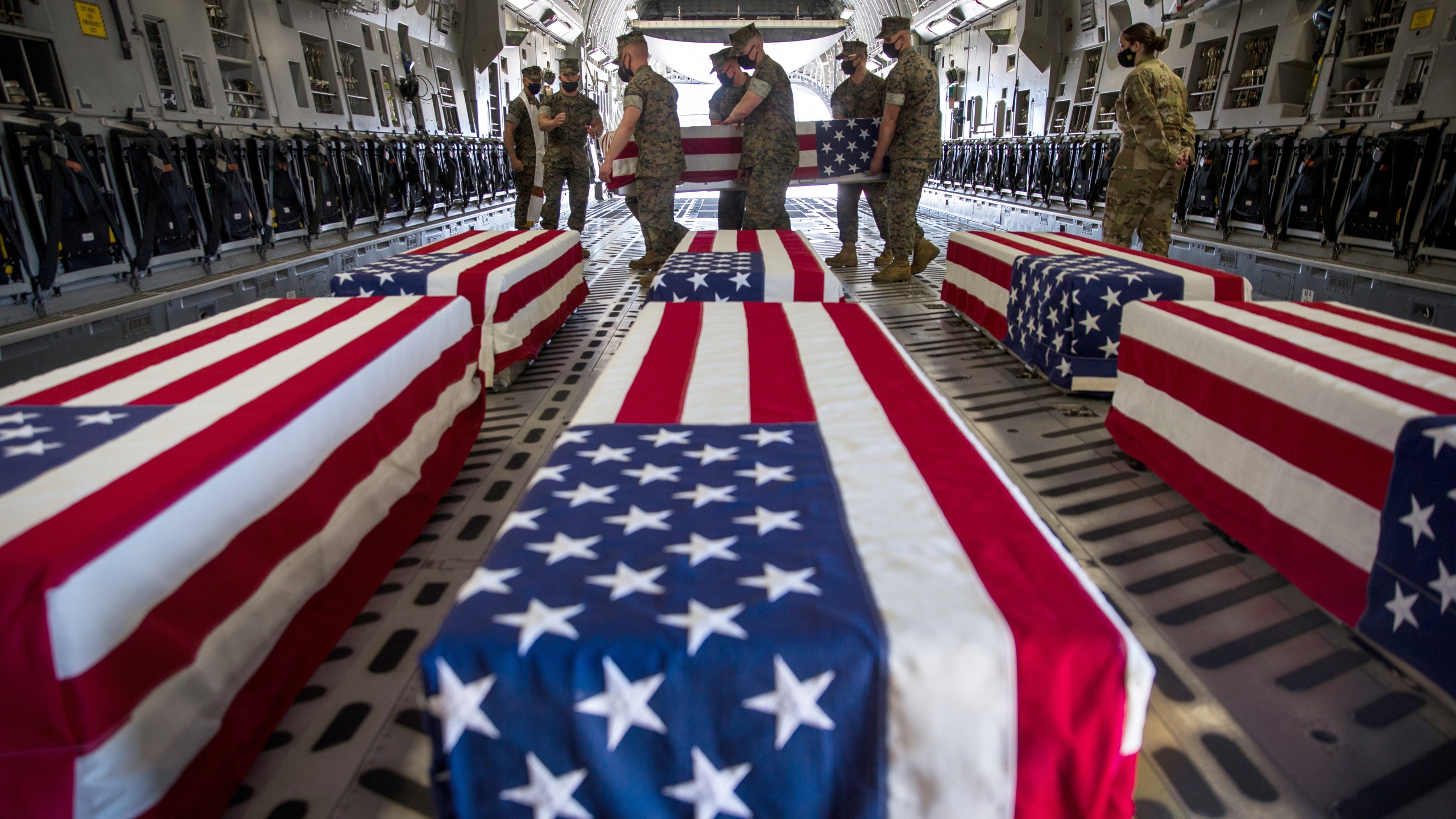 In this photo provided by the U.S. Marine Corps, U.S. Marines and sailors carry a casket inside a U.S. Air Force C-17 Globemaster III at Marine Corps Air Station Miramar, in Calif., Wednesday, Aug. 12, 2020. (Lance Cpl. Brendan Mullin/U.S. Marine Corps via AP)