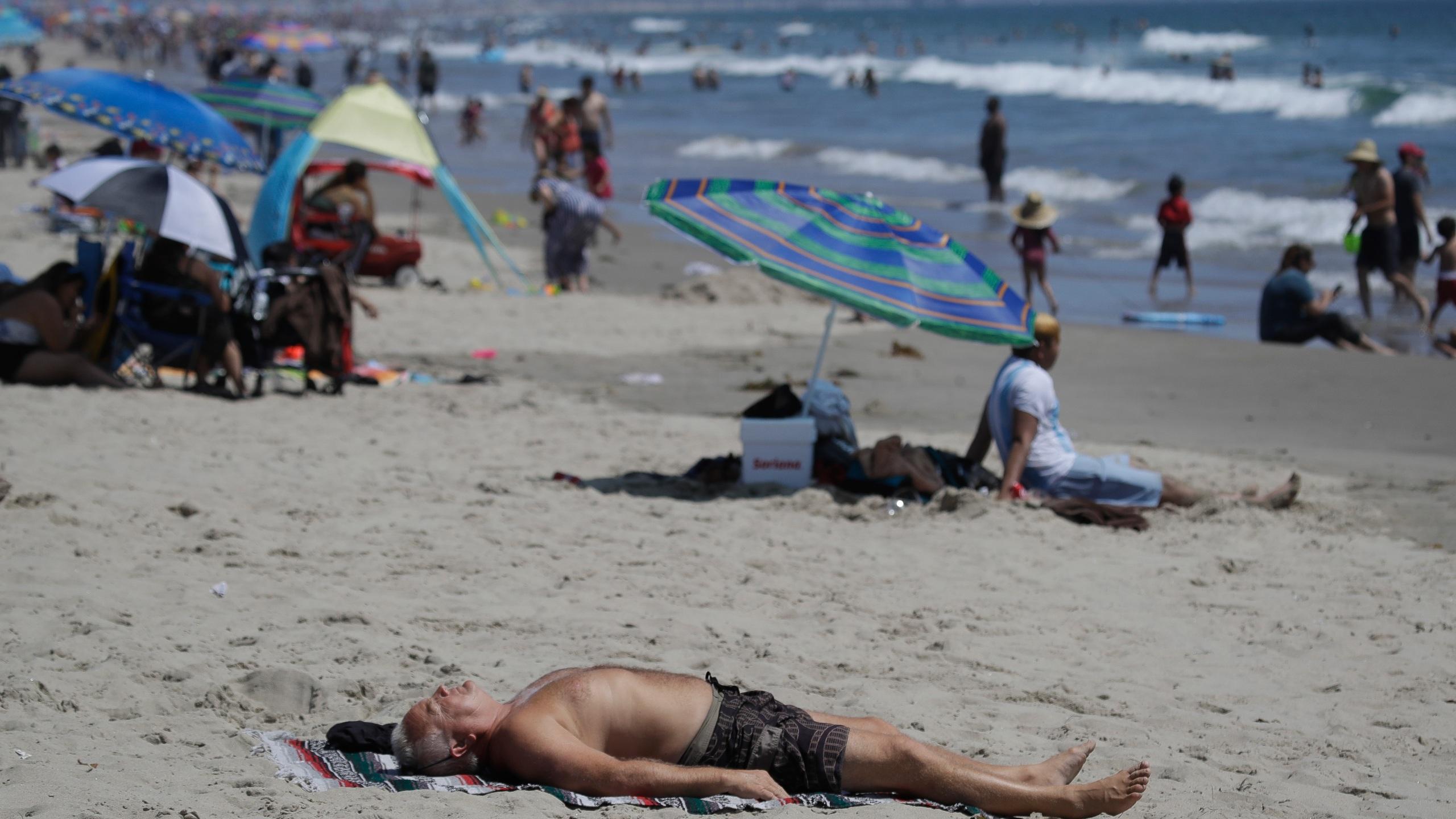 In this Sunday, July 12, 2020, file photo, a man lies on the beach amid the coronavirus pandemic in Santa Monica. (AP Photo/Marcio Jose Sanchez, File)