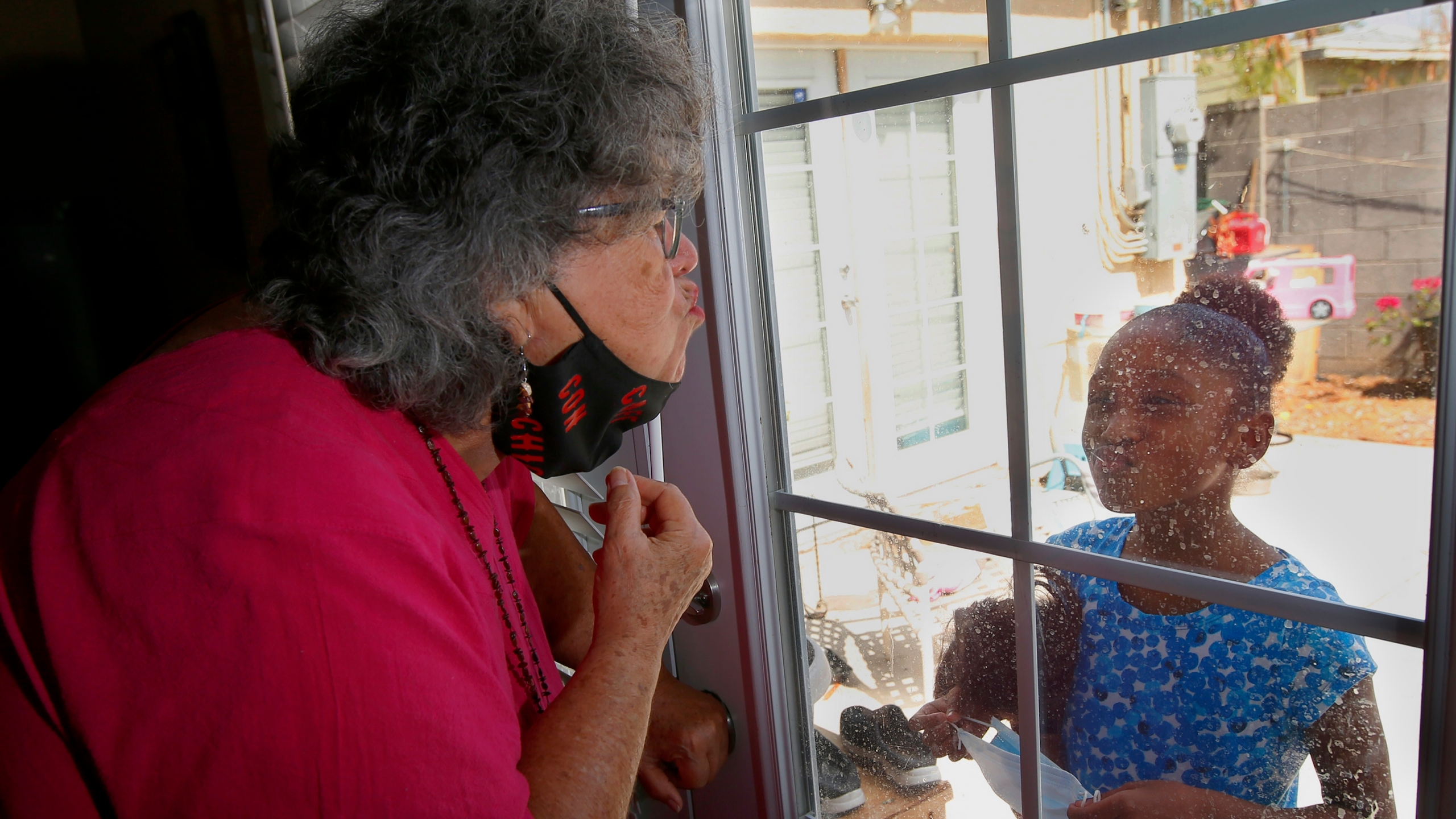 "Zita Robinson, left, who's 77 and diabetic, blows a kiss to her granddaughter Traris ""Trary"" Robinson-Newman, 8, who blows a kiss back to her, Tuesday, Aug. 4, 2020, in Phoenix. (AP Photo/Ross D. Franklin)"