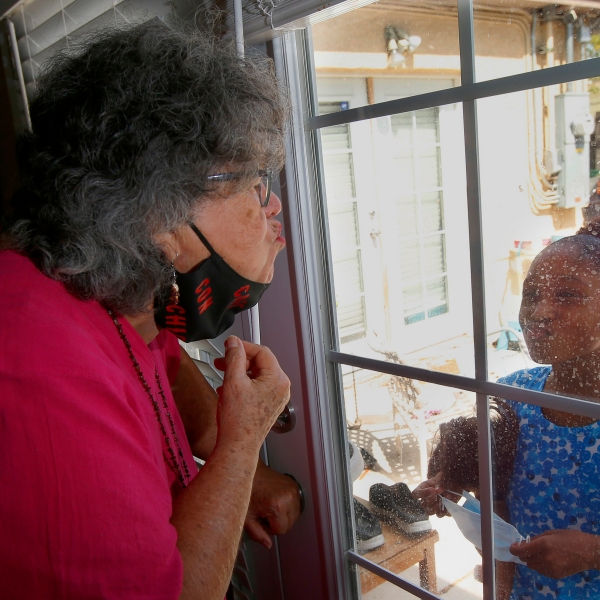 """Zita Robinson, left, who's 77 and diabetic, blows a kiss to her granddaughter Traris """"Trary"""" Robinson-Newman, 8, who blows a kiss back to her, Tuesday, Aug. 4, 2020, in Phoenix. (AP Photo/Ross D. Franklin)"""