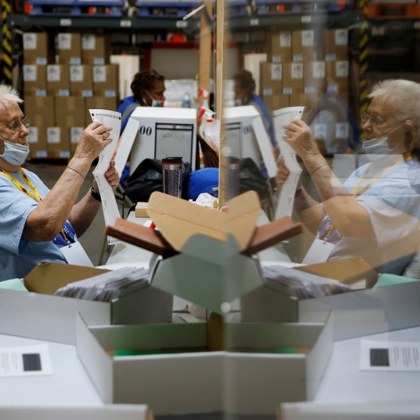 In this June 9, 2020, file photo election workers process mail-in ballots during a nearly all-mail primary election in Las Vegas. (AP Photo/John Locher, File)
