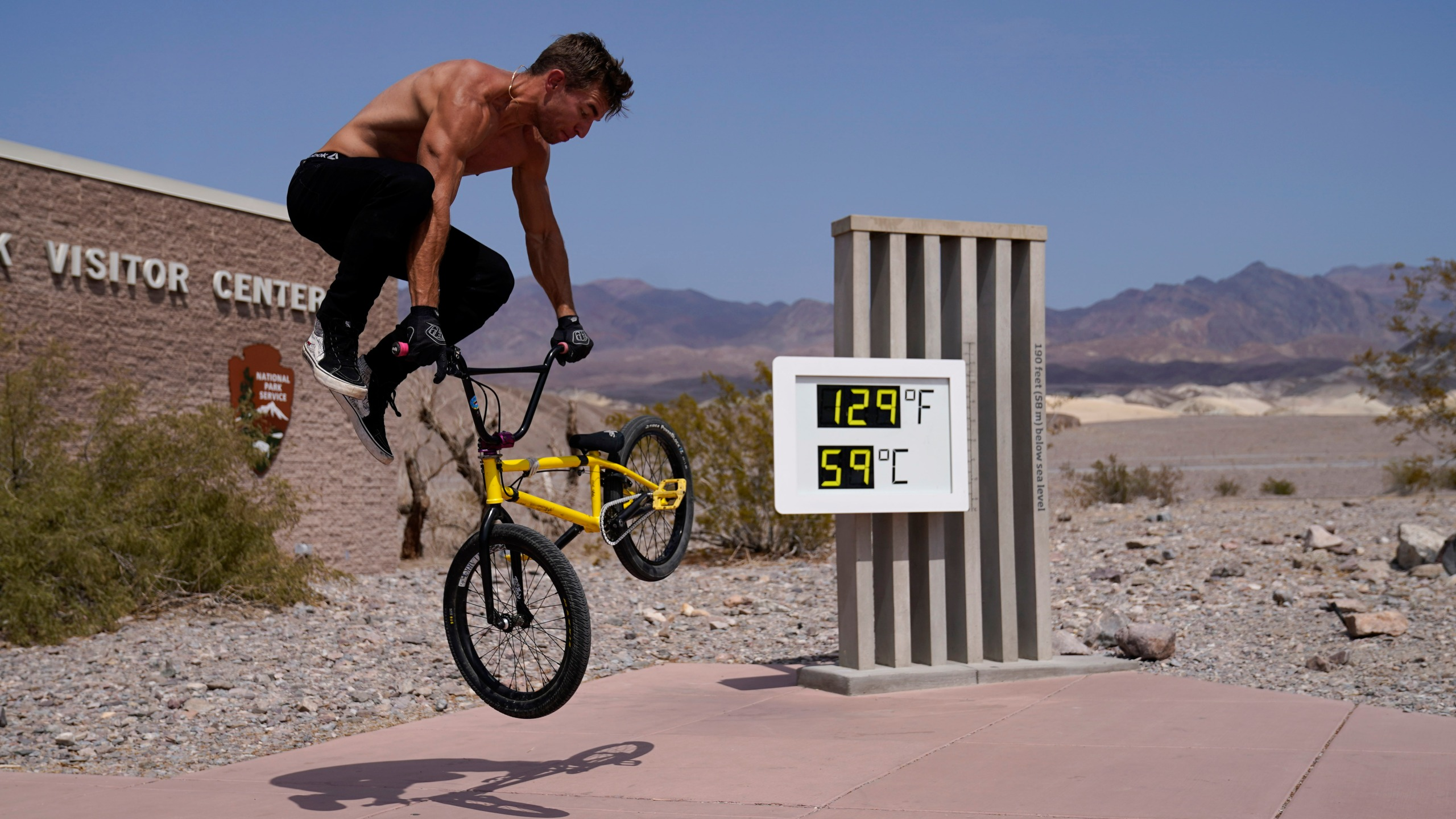 Michael Major rides his bike at the Furnace Creek Visitor Center thermometer Monday, Aug. 17, 2020, in Death Valley National Park, Calif. The thermometer is not official but is a popular photo spot. (AP Photo/John Locher)
