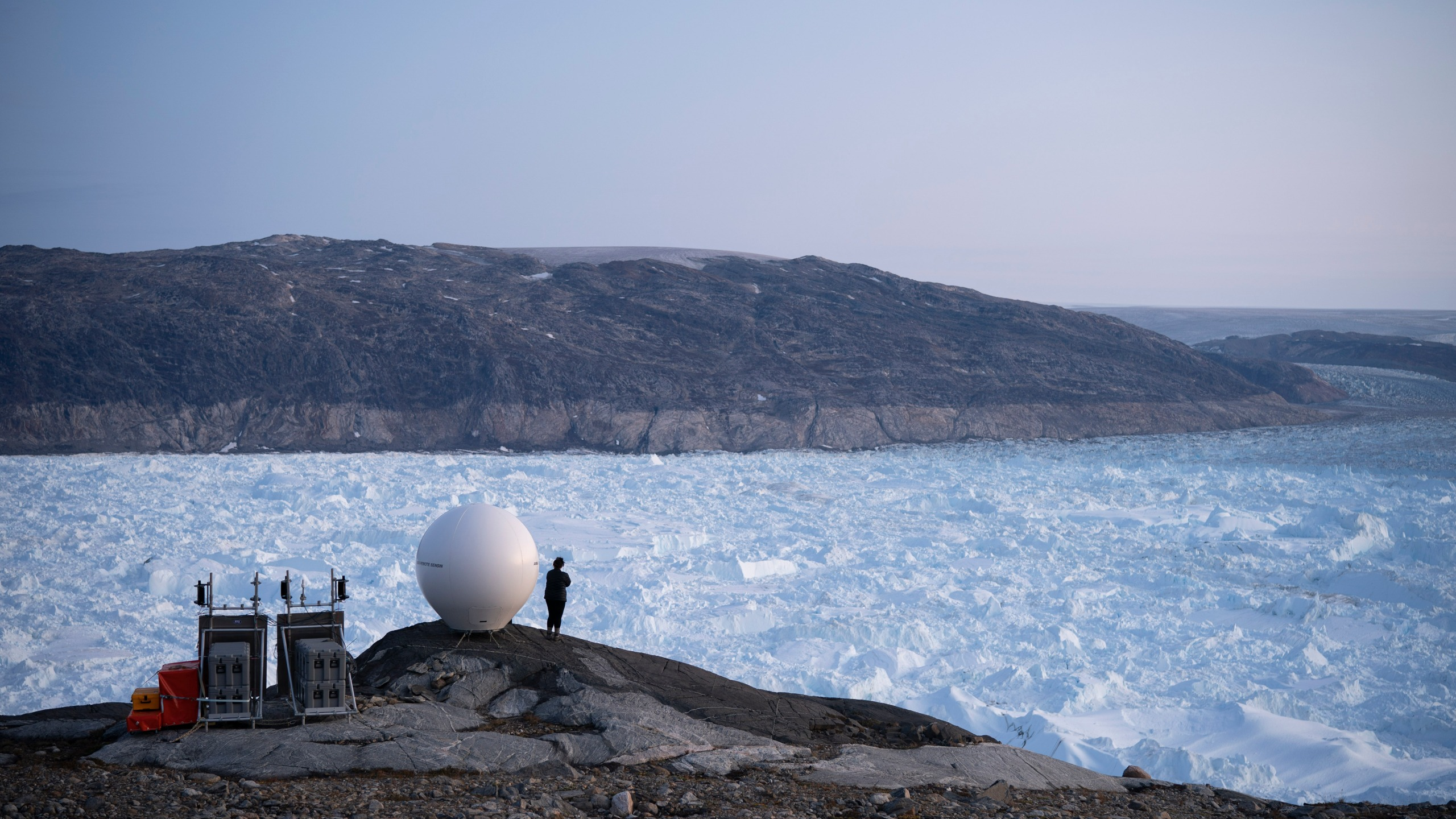 In this Aug. 16, 2019 file photo, a woman stands next to an antenna at an NYU base camp at the Helheim glacier in Greenland. According to a study released on Thursday, Aug. 20, 2020, Greenland lost a record amount of ice during an extra warm 2019, with the melt massive enough to cover California in more than four feet (1.25 meters) of water. (AP Photo/Felipe Dana)