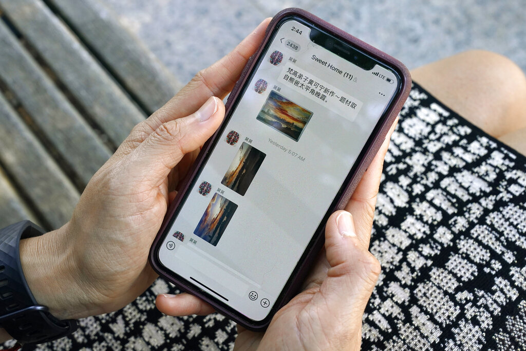 Sha Zhu, of Washington, shows the app WeChat on her phone, which she uses to keep in touch with family and friends in the U.S. and China, on Aug. 18, 2020, in Washington. (AP Photo/Jacquelyn Martin)