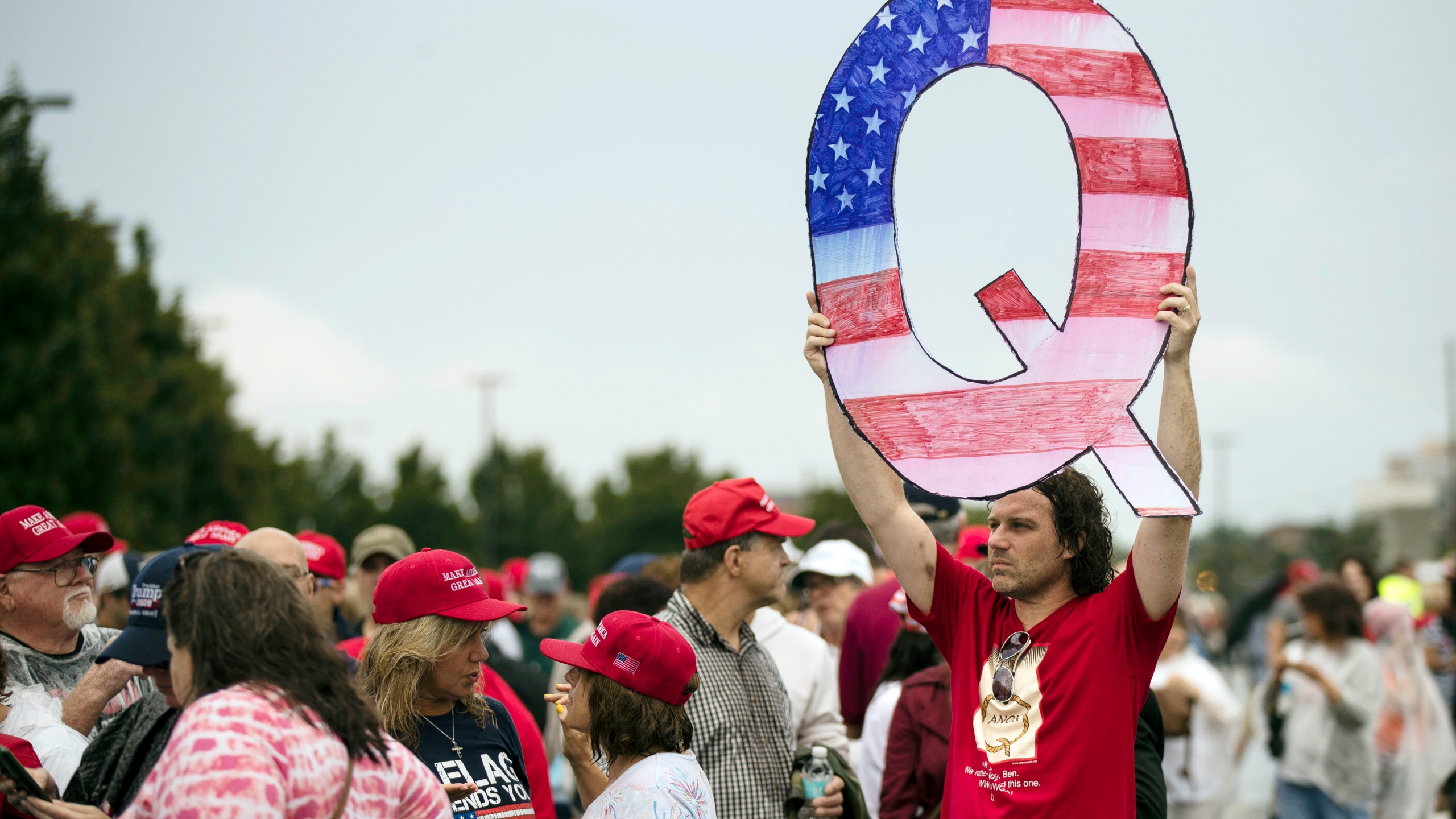In this Aug. 2, 2018, file photo, a protester holding a Q sign waits in line with others to enter a campaign rally with President Donald Trump in Wilkes-Barre, Pa. (Matt Rourke/Associated Press)